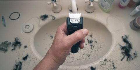 Man holding electric shaver with hair all over sink
