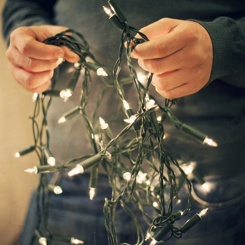 how to fix christmas lights, man holding fairy lights