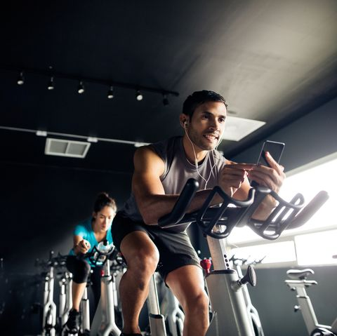Man holding his cellphone while exercising on a gym bike.