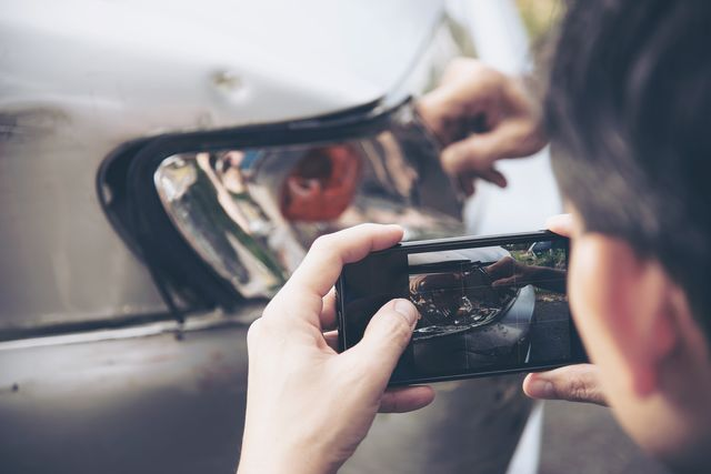 man holding mobile phone by customer showing damaged car
