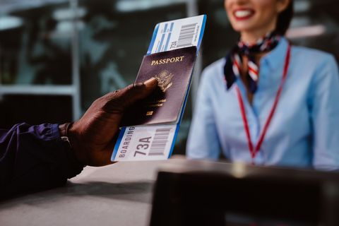 man holding passport and boarding pass at airline checkin counter