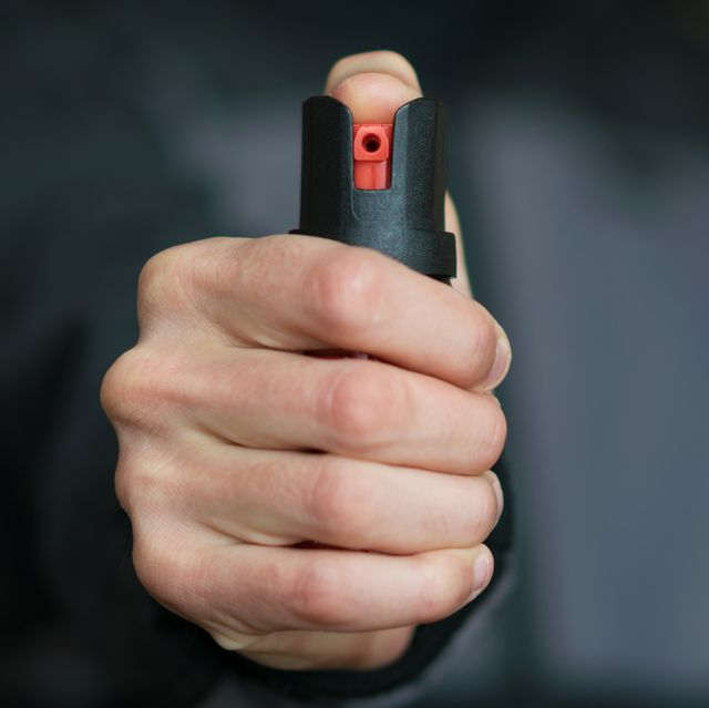 man holding pepper spray tear gas in his hand self defense blur background, close up