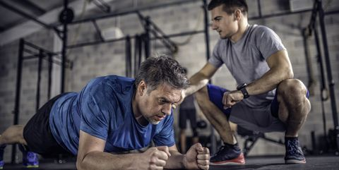 Man holding plank in a gym with trainer watching