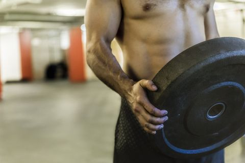 Man holding weight plate and exercising in gym