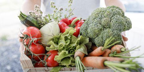 man holding wooden box of organic vegetables closeup