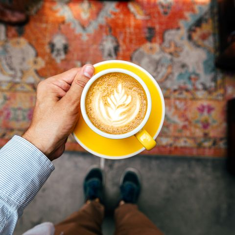 man holding yellow cup with cappuccino, personal perspective view