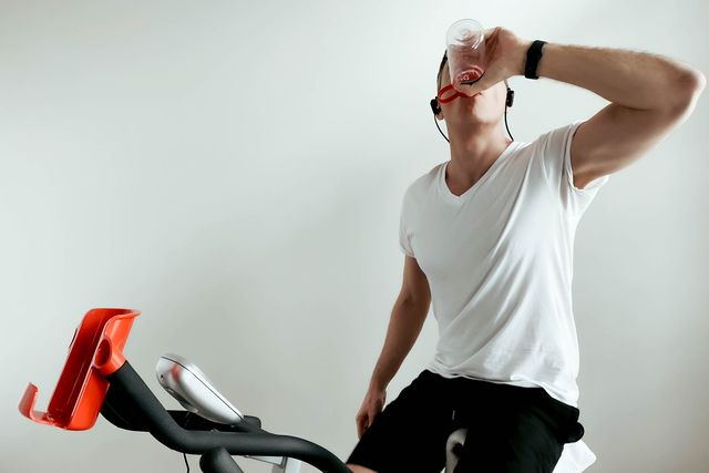 man hydrates during indoor cycling session