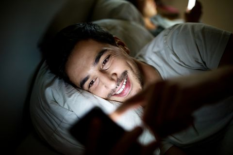 man in bed checking his social media status on smartphone