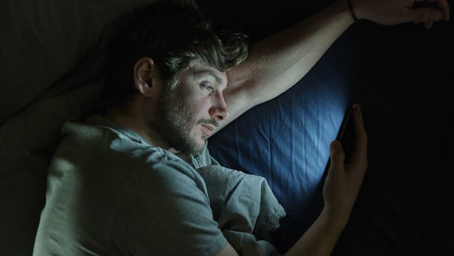 man in bed on smartphone
