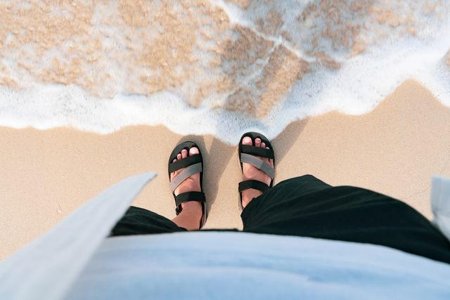 man in black slippers  flip flop feet standing on the beach with a wave of foaming gentle beneath them top view