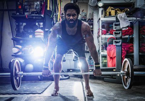 Man in Gym Using Barbells