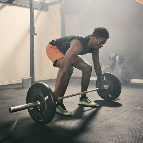 Man in gym weightlifting using barbell