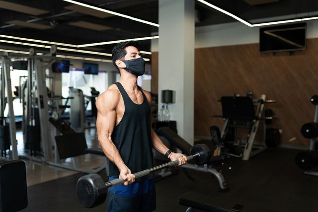 man in his 20s working out in the gym during the pandemic