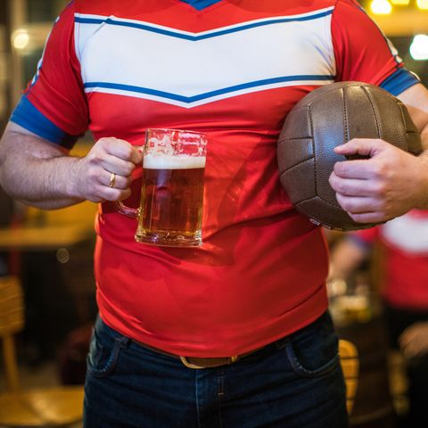 Man in sports uniform holding a beer glass and a ball in a bar