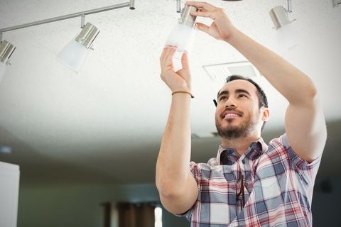 Man installs light fixture in new home