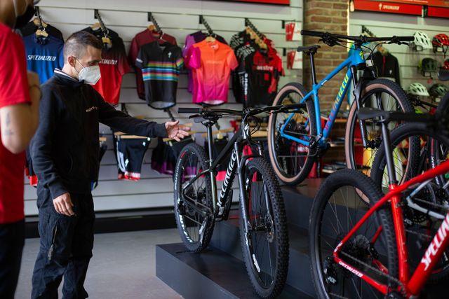 un vendedor de bicicletas muestra varios modelos a un cliente