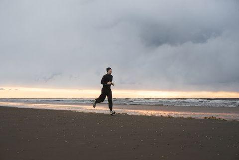 Man jogging at beach against cloudy sky