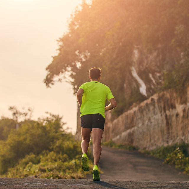 man jogging on a downhill  uphill in suburb mountain road