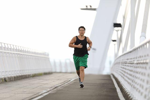 un hombre con sobrepeso corre para perder peso sobre un puente