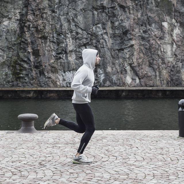 man jogging on street against rock