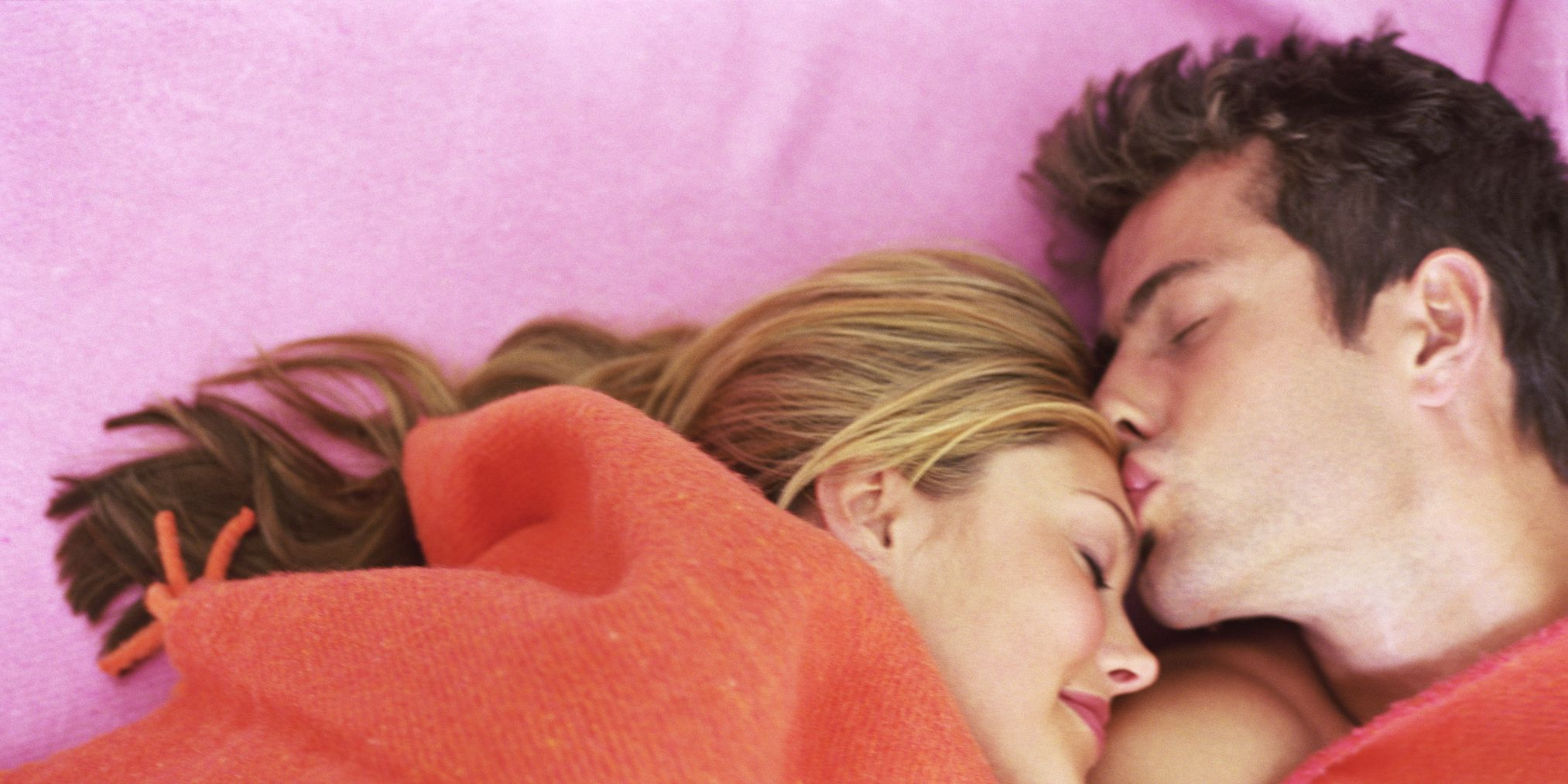 Man kissing resting woman on forehead