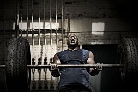 Man lifting barbell with tires attached to ends