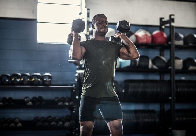 daily undulating periodization   man lifting dumbells at cross training gym
