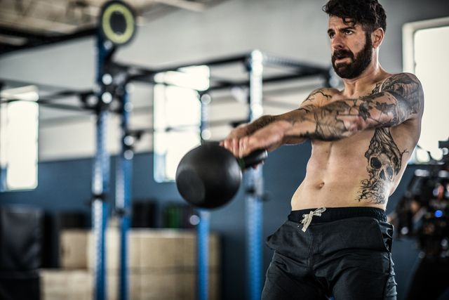 man lifting kettlebell at cross training gym