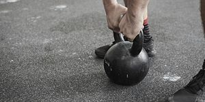 Man lifting kettlebell in cross training gym