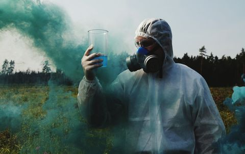 Man Looking At Liquid In Container While Wearing Gas Mask On Field Against Sky