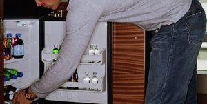Man looking in minibar in hotel room, side view
