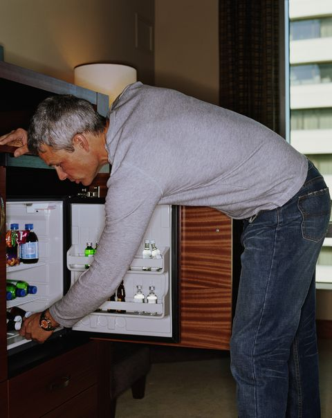 Man looking in minibar in hotel room, side view
