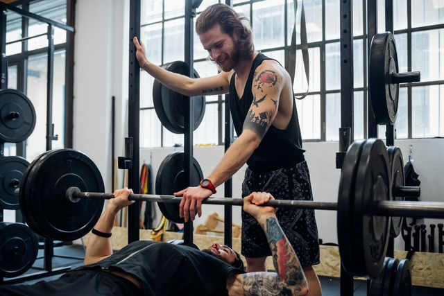 man lying on a weight bench about to bench press with another man standing with his hand on the bar