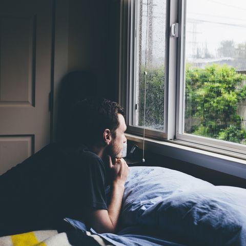 Man lying on bed staring through window at rain