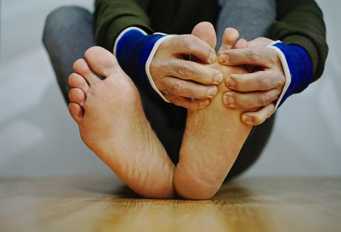 A man massages his foot at the gym