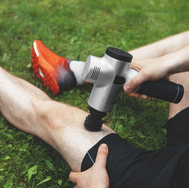 man massaging leg with massage percussion device after workout