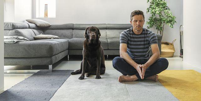 man meditating with his pet dog