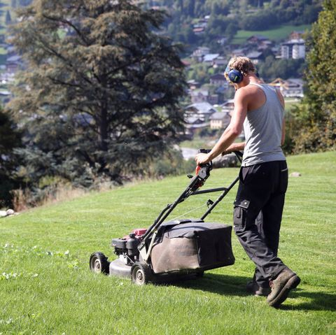 Man mowing the lawn.  France.