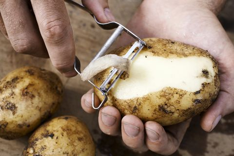 man peeling potato