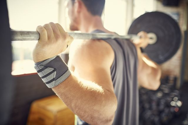 man picking up barbell while wearing sweat band in gym