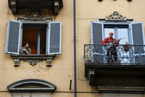 A man plays guitar from the balcony of his home as a man...