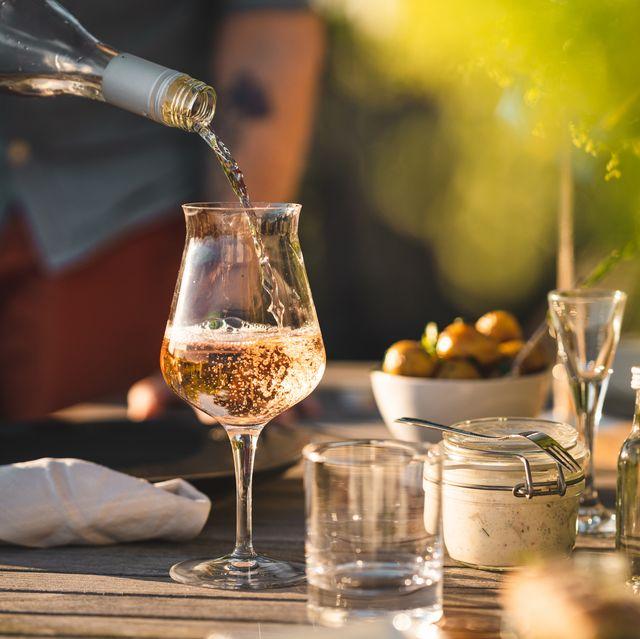 man pouring up rose wine at midsummer dinner