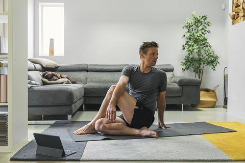 man practising yoga at home