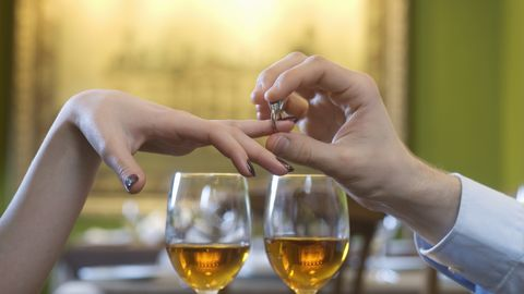 Man putting engagement ring on woman's finger above white wine glasses, close-up of hands