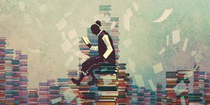 man reading book while sitting on pile of books