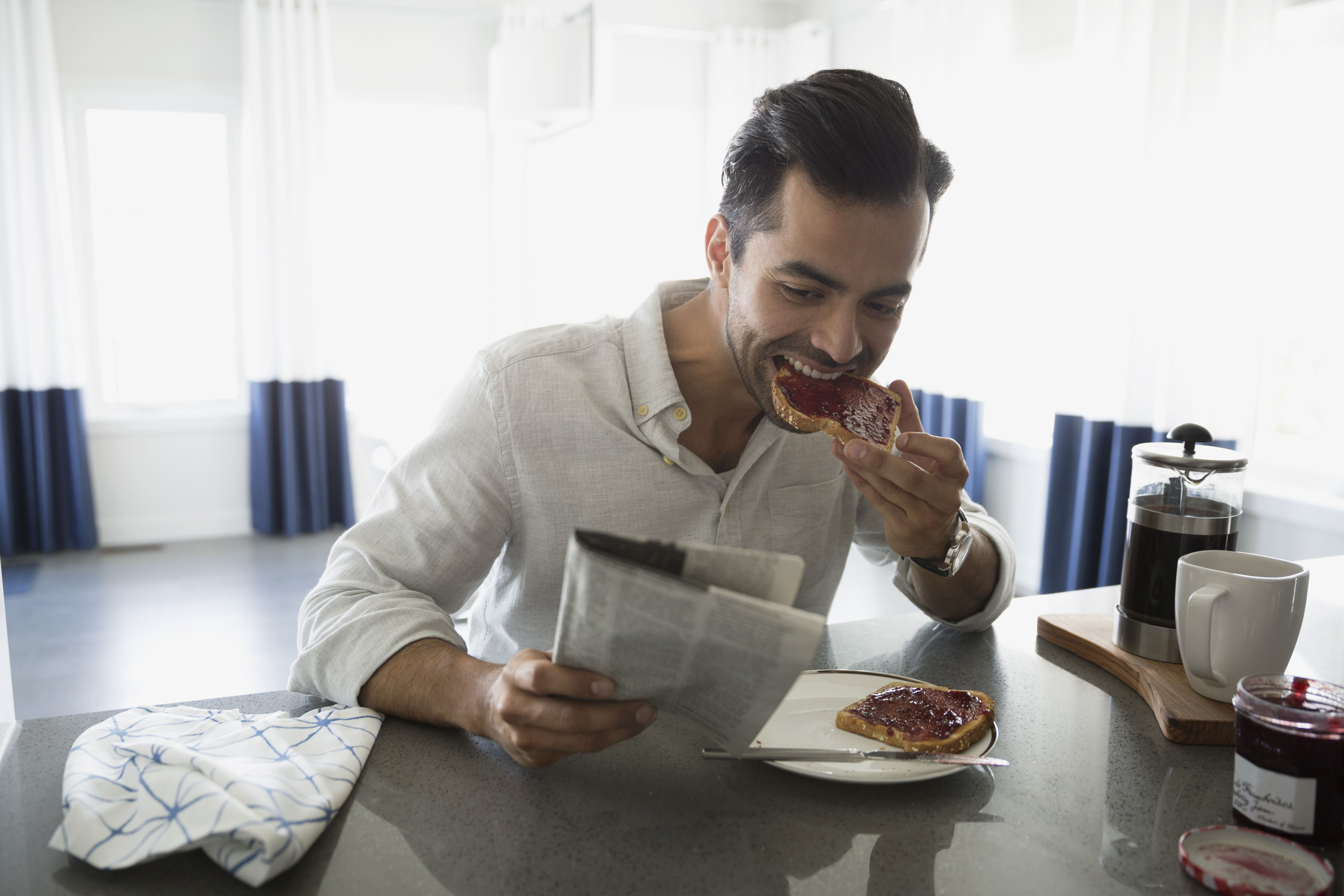 Man reading newspaper and eating toast in kitchen