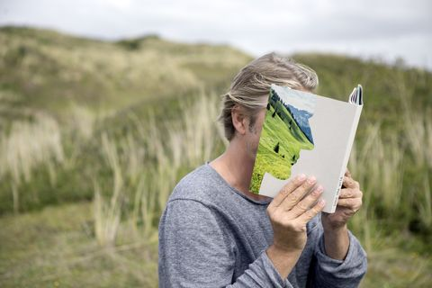 Man reading story book in the dunes, covering his face