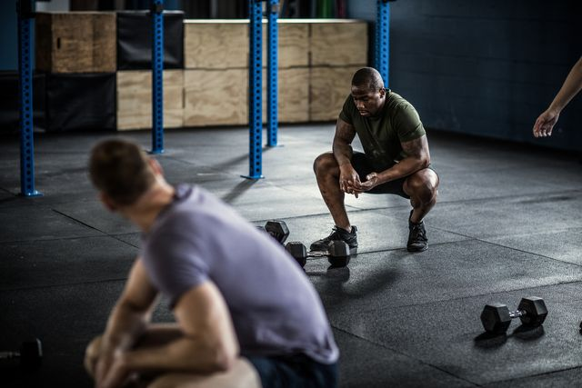 man resting in between sets at cross training gym