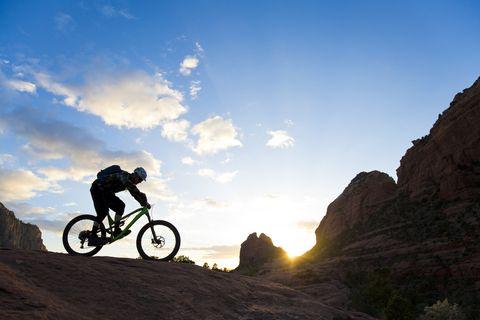 a man rides his enduro style mountain bike at sunset in sedona, arizona, usa