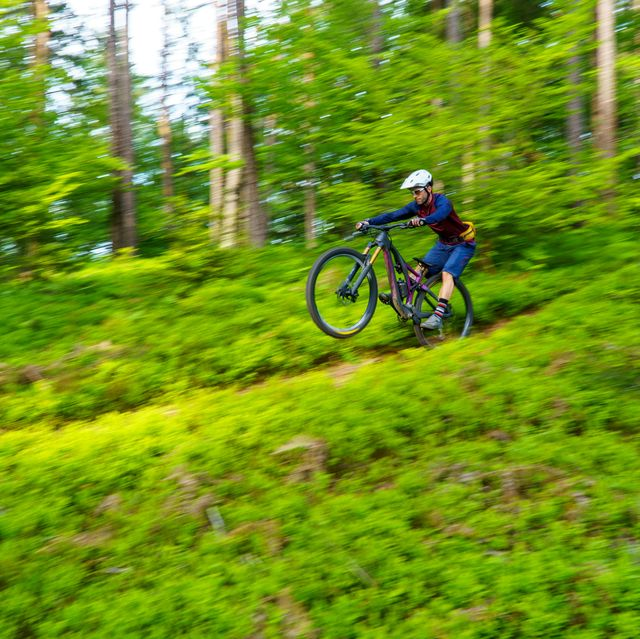 man riding a mountain bike on a trail in the forest, klagenfurt, austria